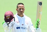 A Queensland Sheffield Shield player raises his bat with his left hand as he celebrates a century.