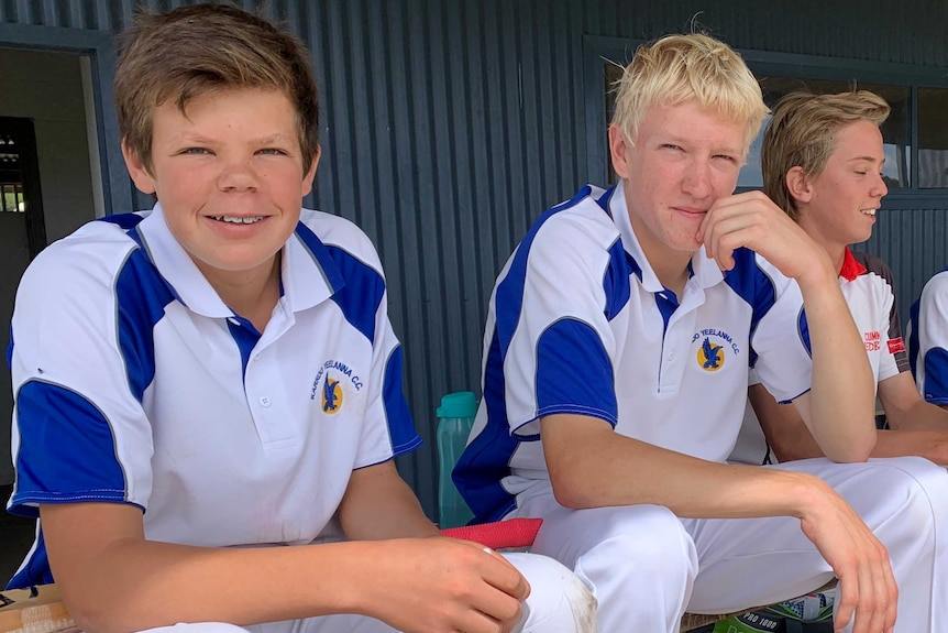 Two boys in cricket whites with blue trim, looking at the camera