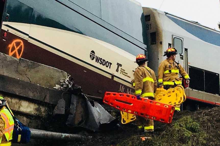 Emergency workers carry stretchers next to a derailed train.
