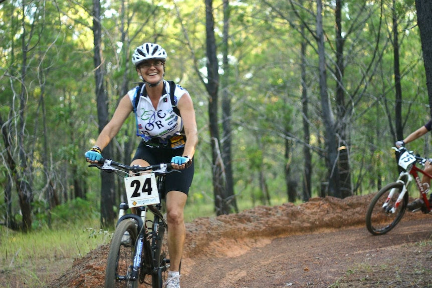 a woman on a mountain bike riding in a competition in a pine forest.