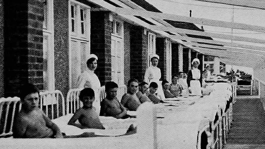 A black and white image of young boys lying in hospital beds on a long outdoor veranda