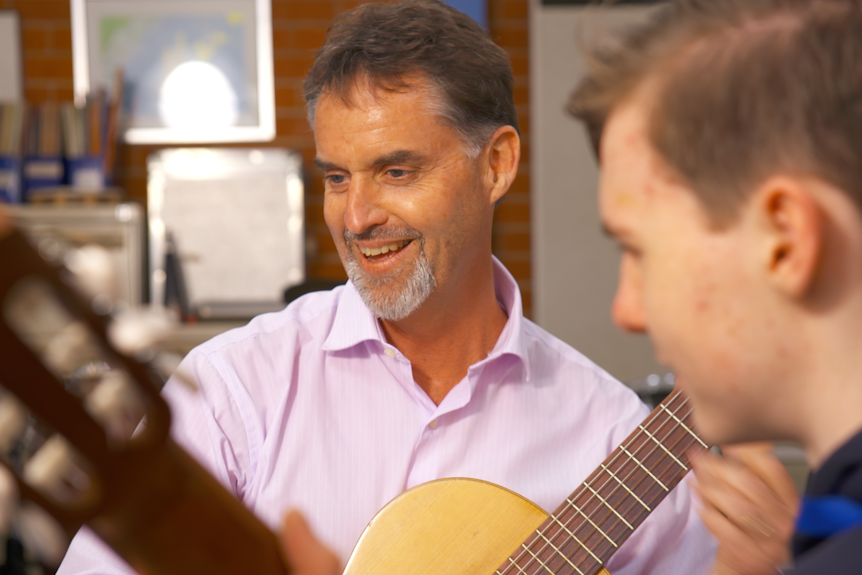 A man smiles as he and a boy sit to play classical guitar.