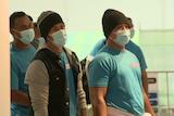 A group of men wearing face masks