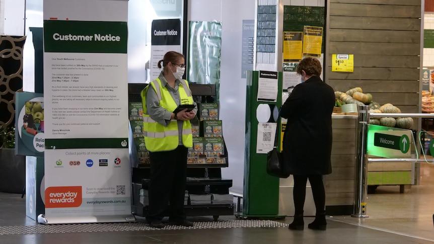 A person scans a QR code before entering a shop.