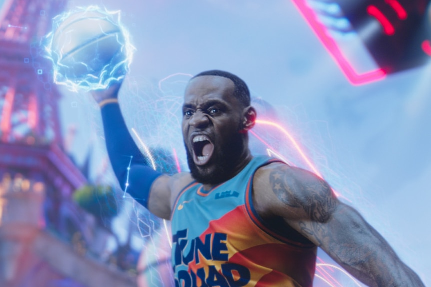 LeBron James jumps up to dunk a basketball with one hand, his mouth open as he yells with joy