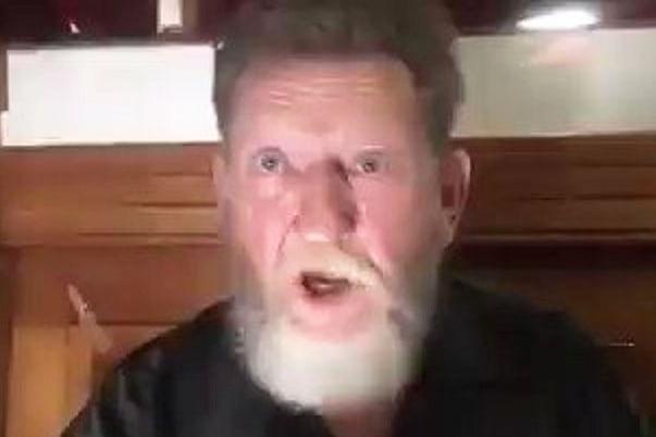 Video still ofJohn James Wilson speaking.