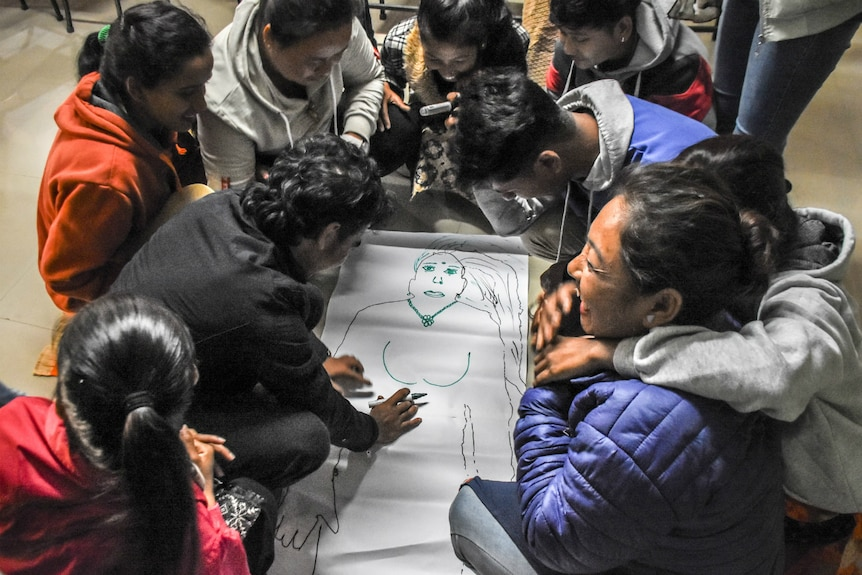 People sit around a drawing of a woman's body at the Sounali crossing on the Nepal-India border.