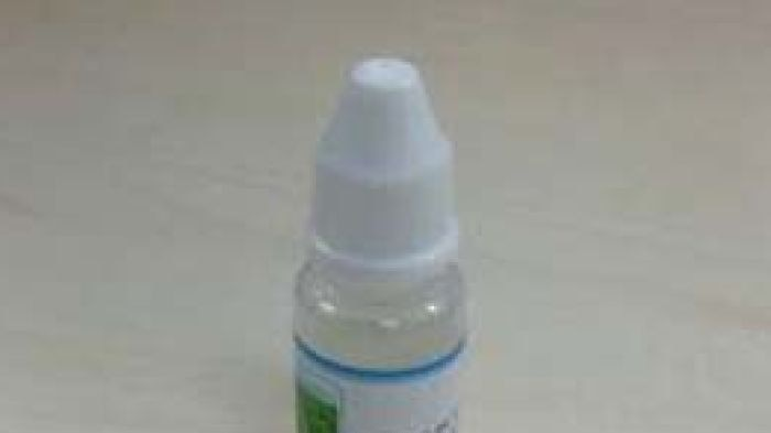 An e-cigarette sits next to a vial of nicotine.