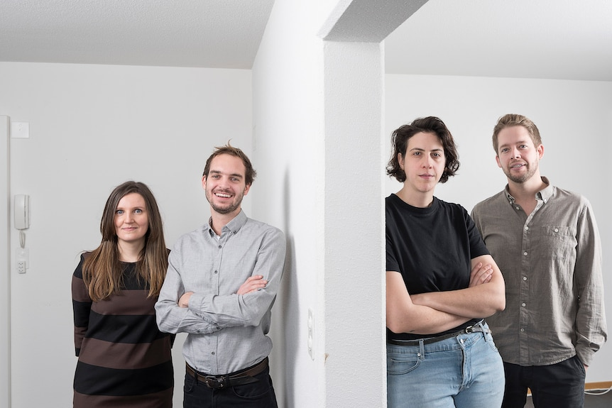 Four young architects standing in a white space, separated by a wall