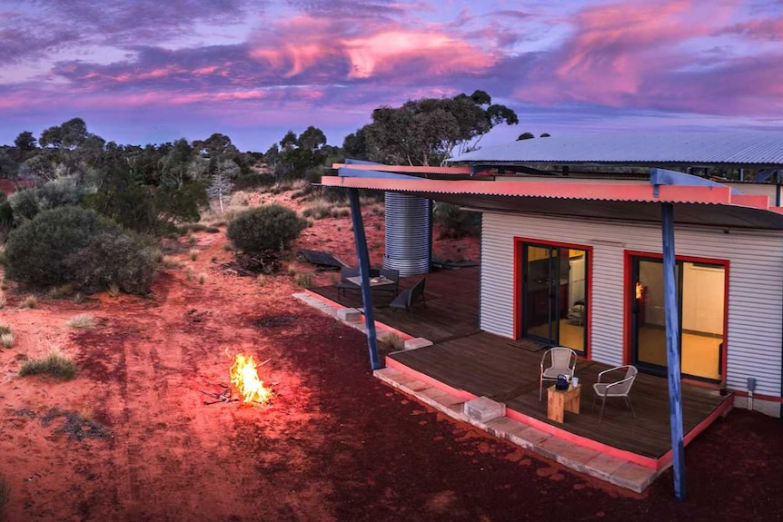 An accommodation facility in bushland, at sunset.