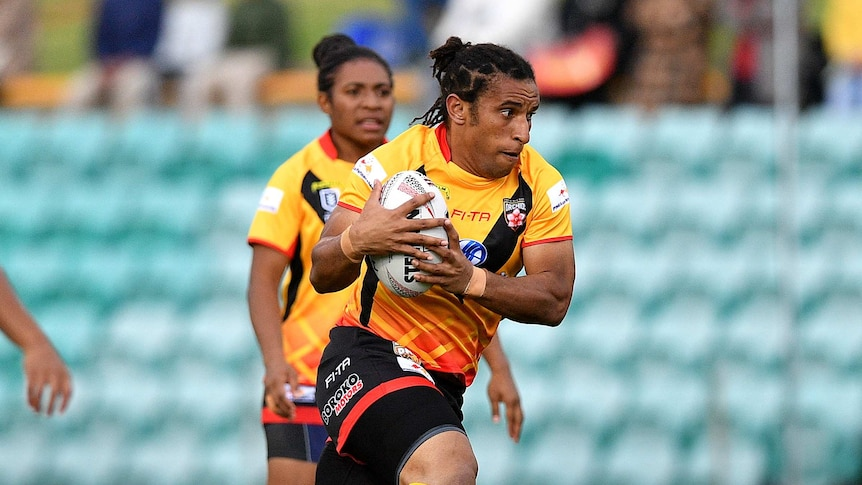 Elsie Albert playing with the PNG Orchids, she is holding the ball and running hard.