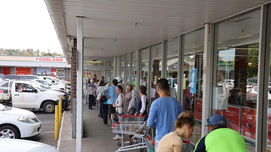 20 people line up outside a supermarket.