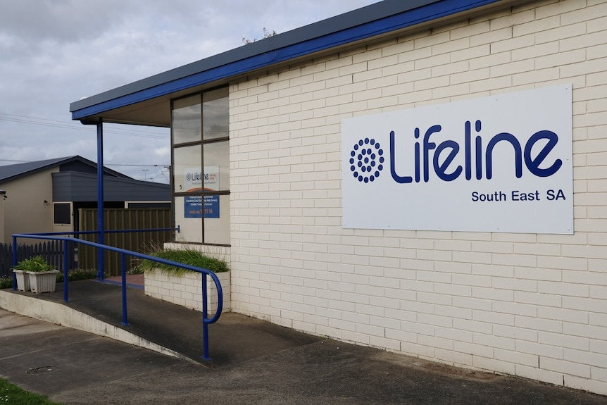 """A white brick building with a white and blue sign that reads """"Lifeline South East SA"""""""