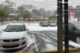 A supermarket car park covered in hail.