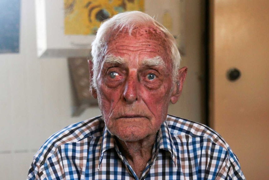 An old man wearing a checked shirt sits on a chair with his hands clasped in front of him