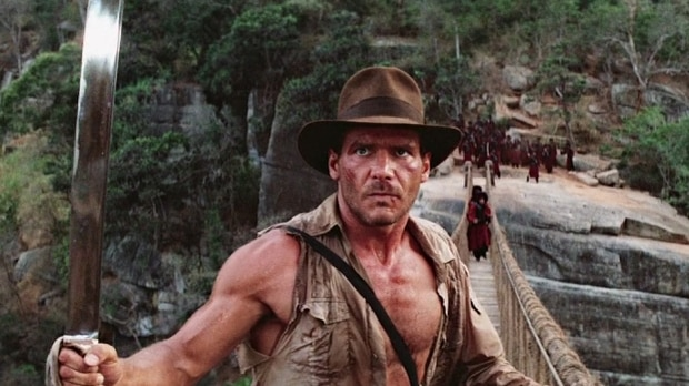 Harrison Ford in at hat on a bridge in a scene from the Temple of Doom