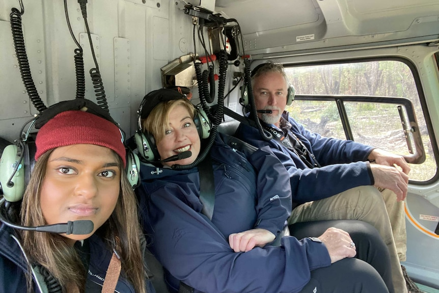 three people in a helicopter seat