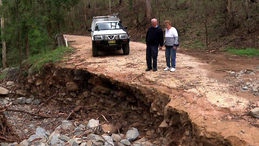 An elderly couple inspect damage to a dirt road which has left a large crater.