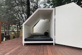 An accommodation pod that contains a mattress and phone charger.