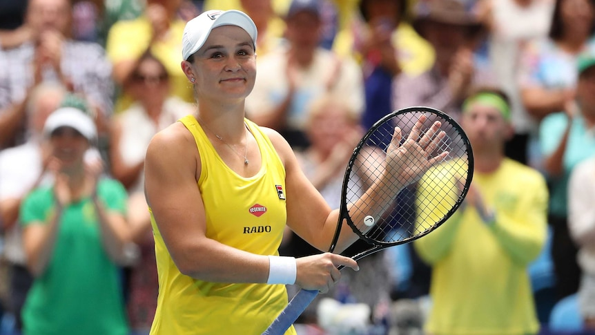 A woman wearing yellow sports singlet and white cap smiles holding tennis racket, while blurred crowds stands clapping behind.