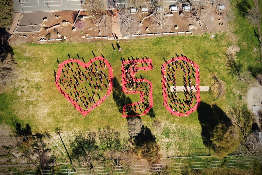An aerial photo of a big heart and number 50 made by students.