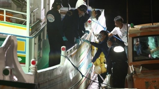 """Taiwan policemen inspect bullet holes on the """"Guang Ta Hsin 28"""" fishing boat."""