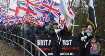 Dozens of Britain First group members march through Telford holding Union Jack flags