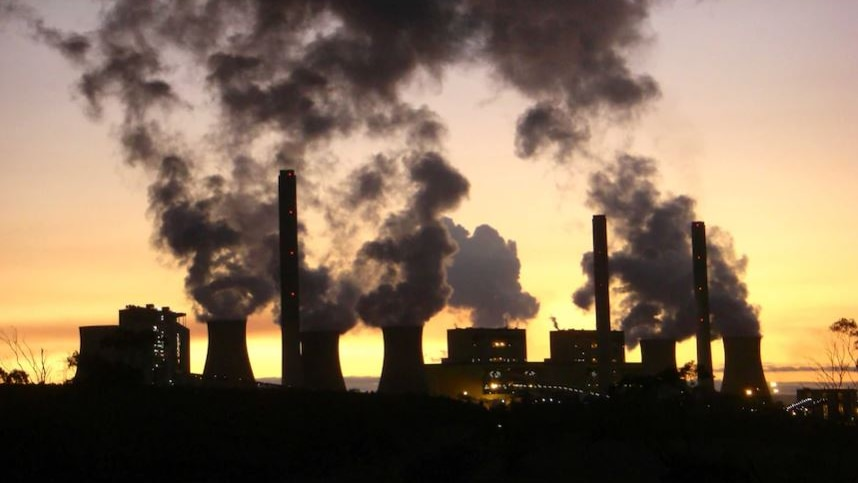 The silhouette of a smoking gas plant is contrasted against a golden sunset.