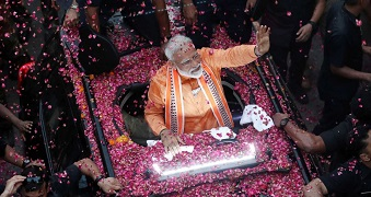 A man in an orange outfit waves from a car that is covered in pink rose petals.