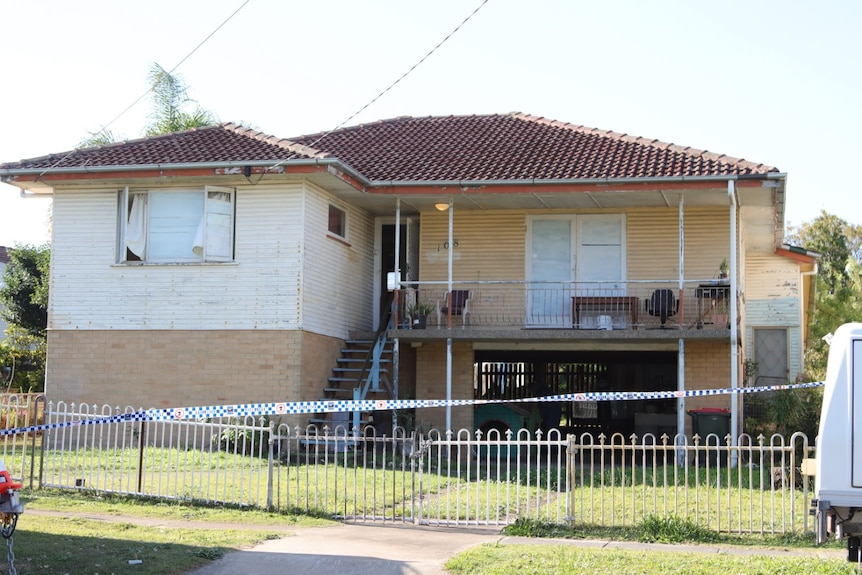 A two storey house with police tape across the front.