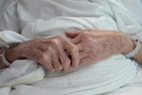 A file photo of an elderly patient's hands with a hospital identification band.