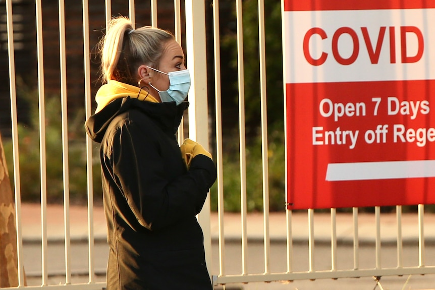 A close-up side-on shot of a woman wearing a face mask in front of a fence with a red COVID clinic sign on it.