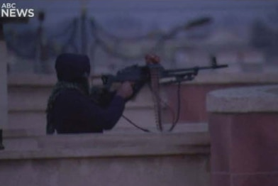 A figure dressed in black stands on a rooftop terrace, aiming a machine gun.