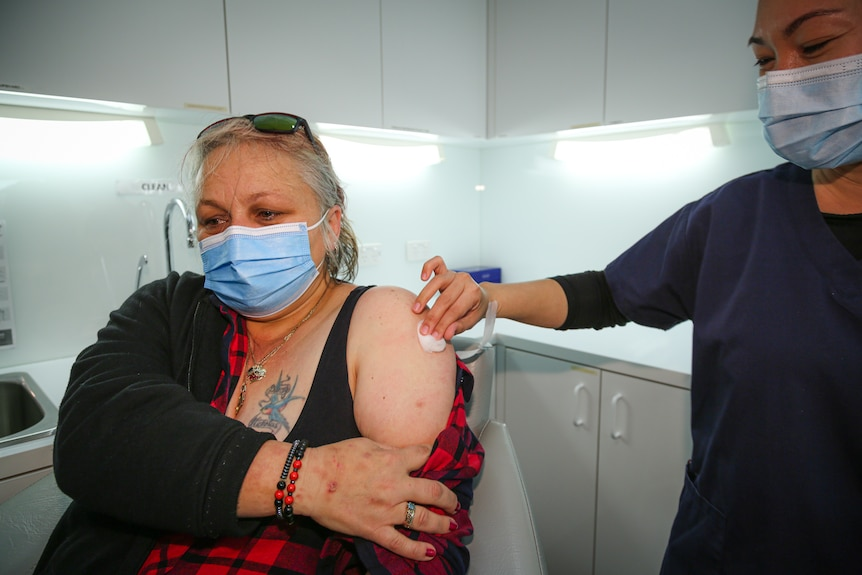 A woman wearing a mask holds her shirt after getting a COVID-19 vaccination.