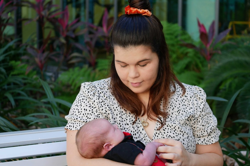 Brunette woman in floral dress looking down at three week old son in her arms at hospital courtyard.