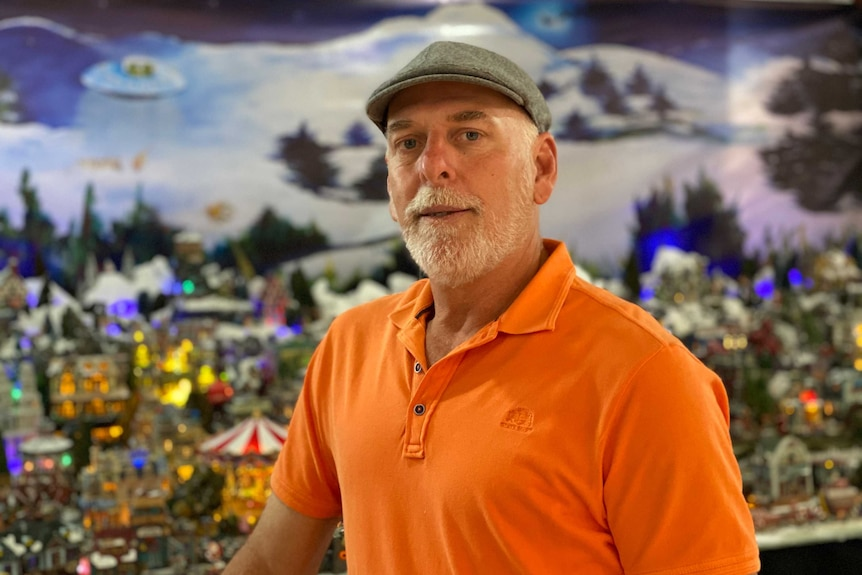 Older man stands in front of miniature Christmas village.