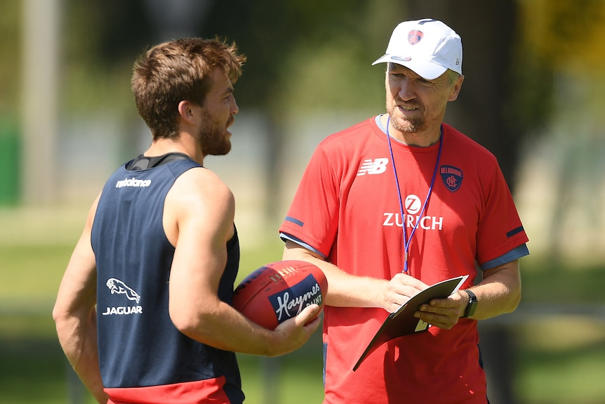 AFL fitness coach talking with a player during training