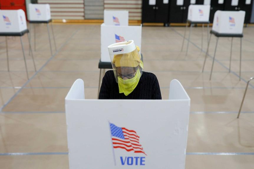 Jocelyn Bush, a poll worker at the Edmondson Westside High School Polling site, cleans each station after a ballot is cast
