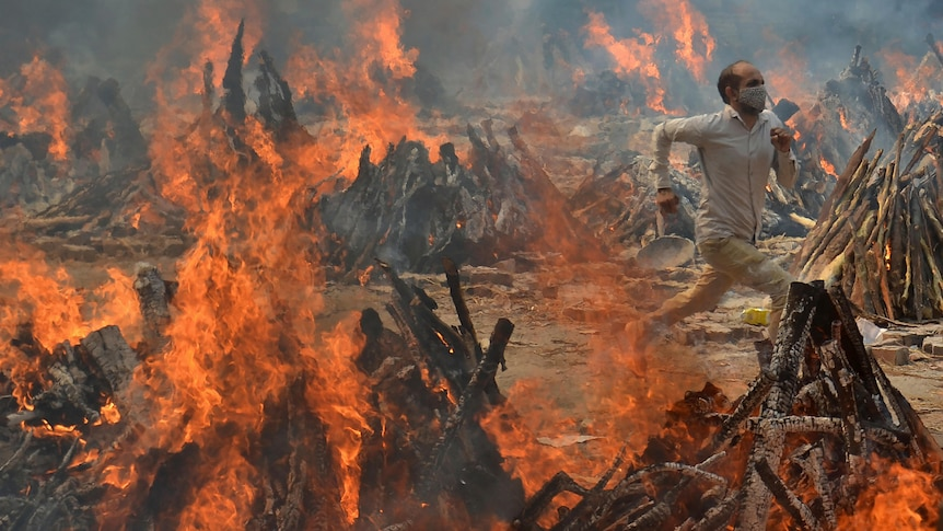 A man runs to escape heat emitting from the multiple funeral pyres.