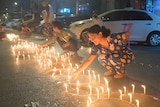 People light candles on the street during a candlelit vigil in Yangon