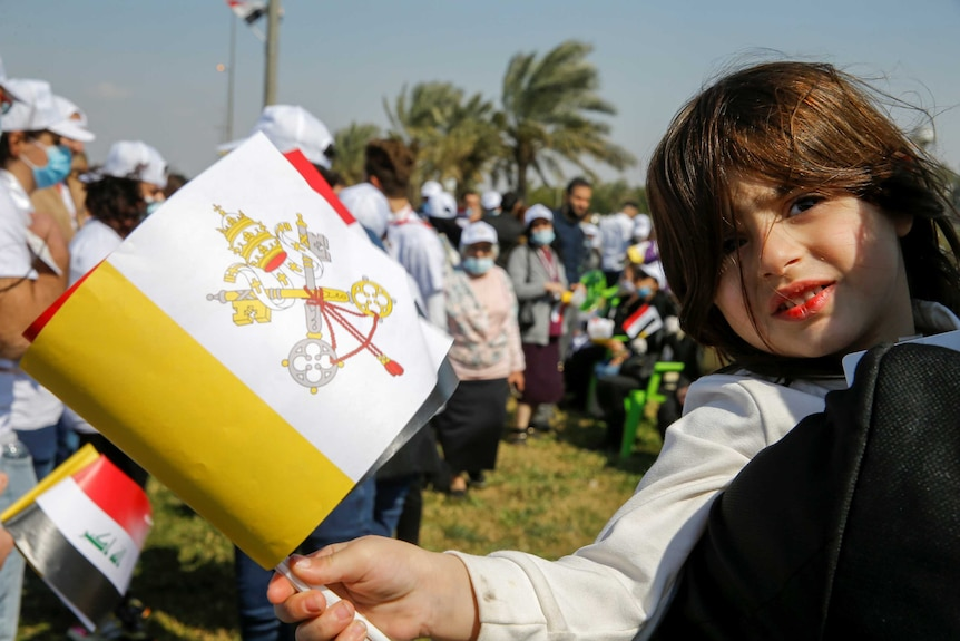 A young girl smiles at camera and carries a white, yellow and red flag in a crowd on a sunny day.