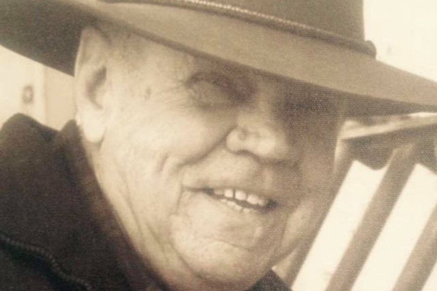 An older man wearing an akubra smiles as he looks at the camera.