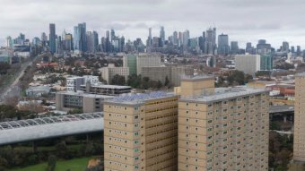 Two public housing towers with the Melbourne city skyline in the background.