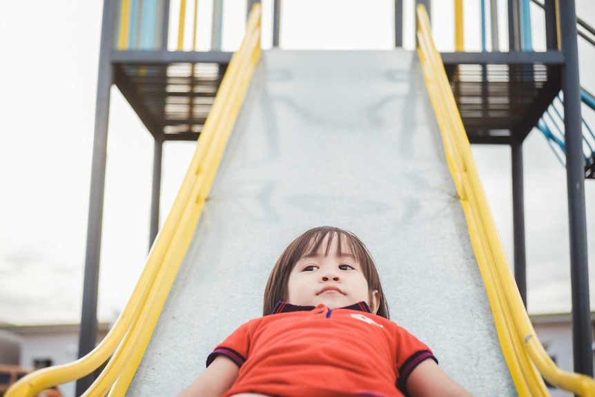 Cute little boy about three years old on a playground slide
