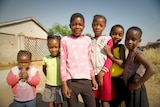 A group of young Zimbabwean girls stands together and look at the camera, some smiling