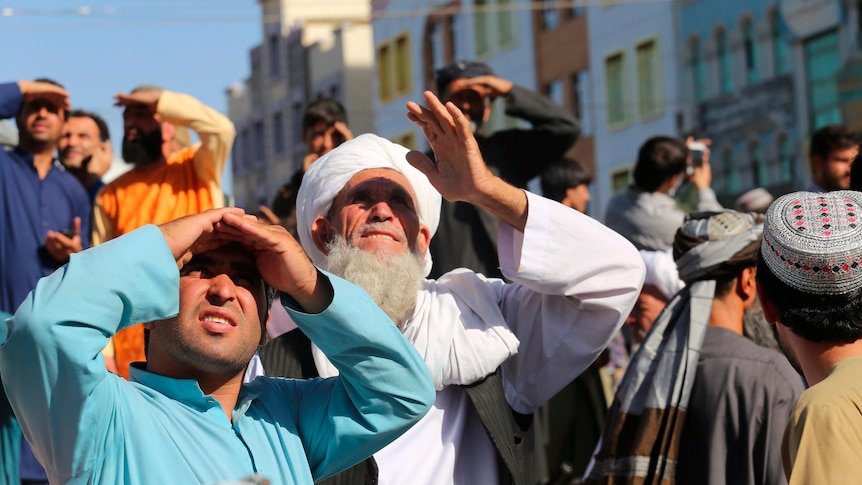 People look up at a dead body hanged by the Taliban from a crane in the main square of Herat