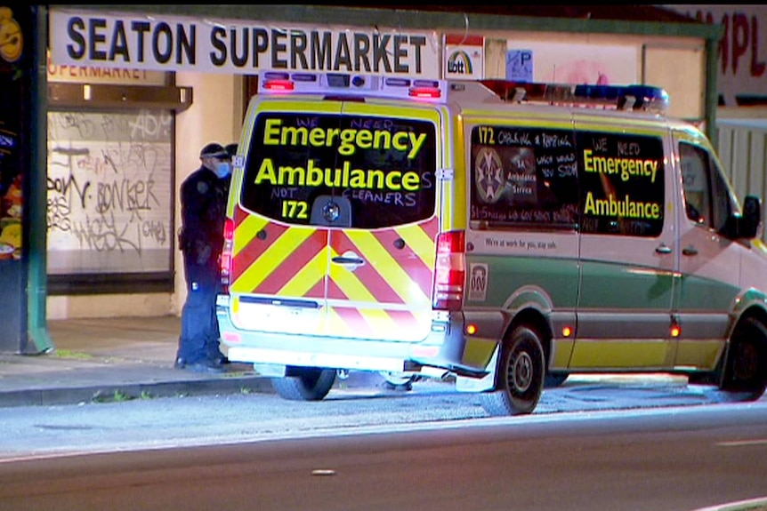 An ambulance and police officers outside a supermarket.