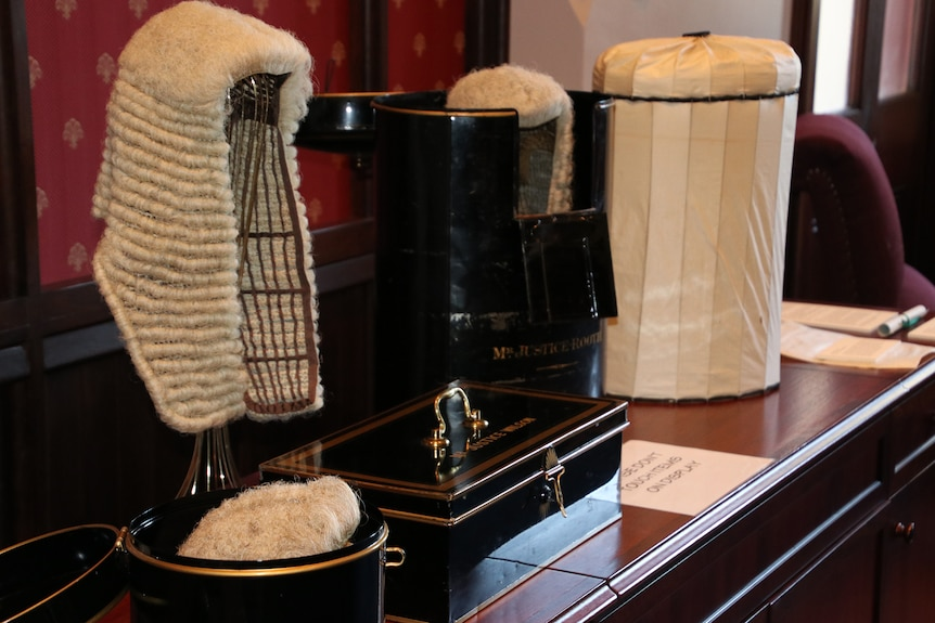 A horse hair judge's wig sitting on a stand, with a black box in front of it.