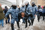 Four police officers in arctic camo carry a protester away. They are wearing heavy armor.