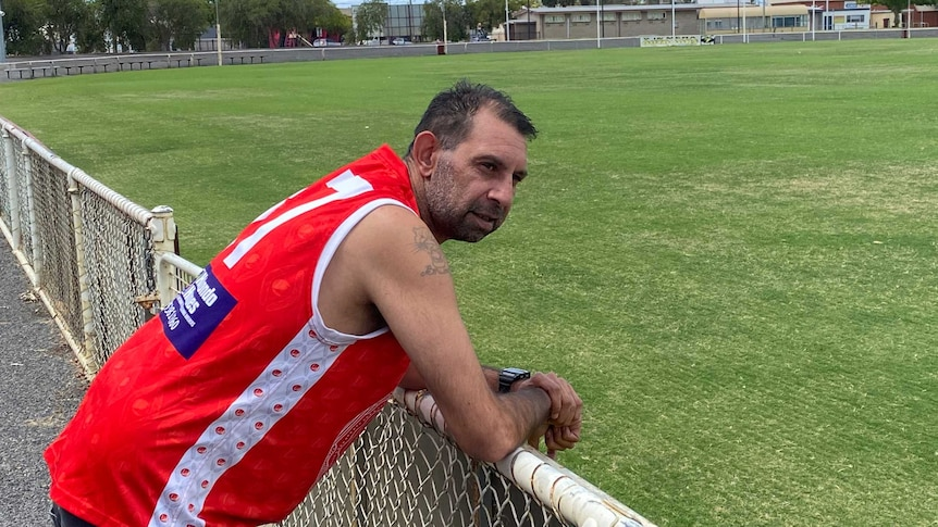a man wearing a red football guernsey leans on the fence of a country aussie rules oval